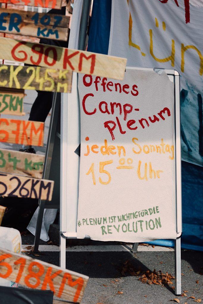 """Schild """"Offenes Camp-Plenum. Jeden Sonntag 15 Uhr"""""""