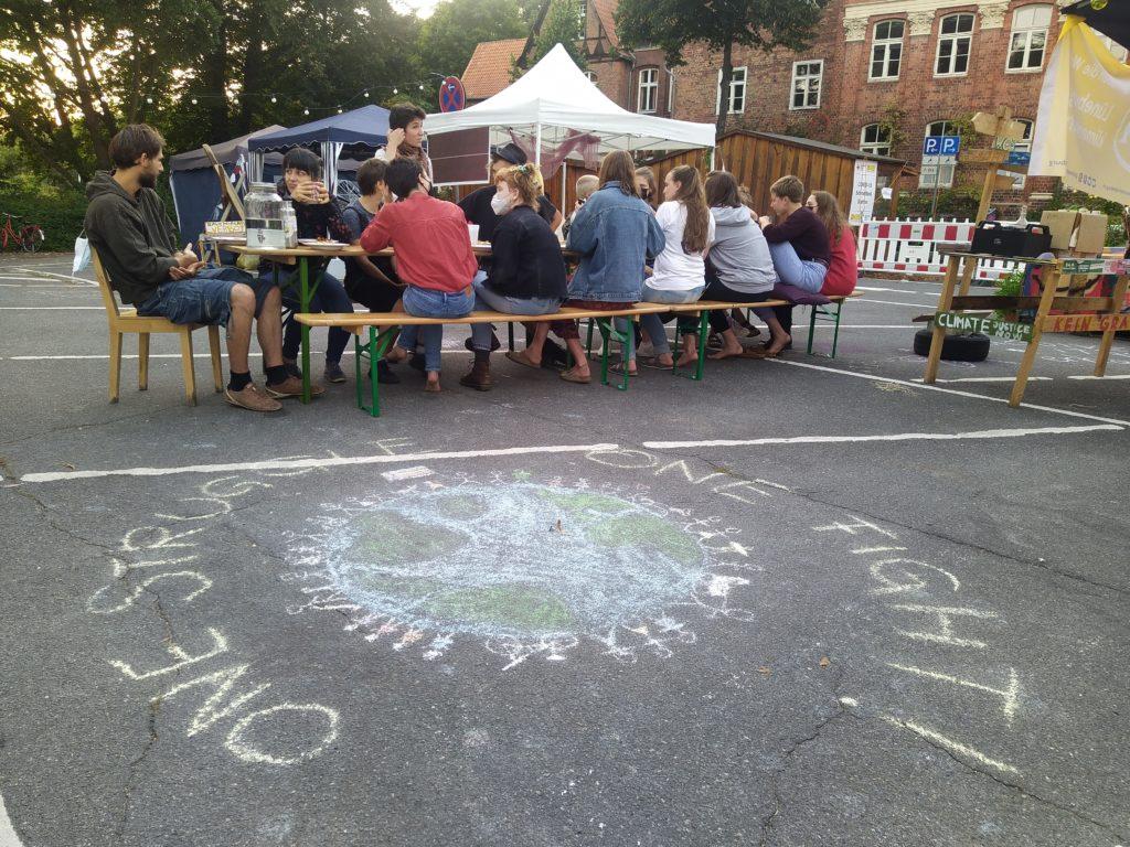 Menschen auf dem Klimacamp & Kreideverschönerung des Platzparks